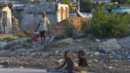 A Haitian man (L) carries a bucket filled with waste to be discarded, in a slum area in Port-au-Prince, Haiti, Dec. 17, 2012.