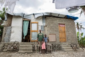 coteaux_farmer_serde_ranodio_stands_in_front_of_the_familys_destroyed_house_with_his_childrenlowerres